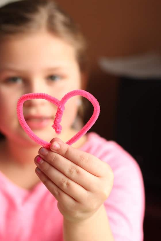 kid holding heart shaped pipe cleaner