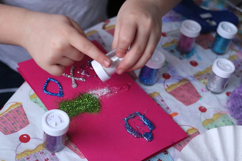 Child shaking glitter into hot glue