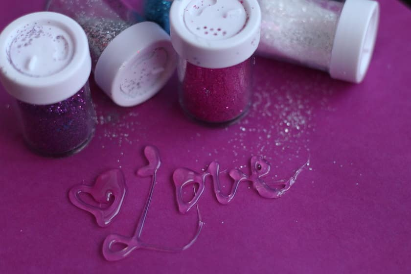 Love written in hot glue and glitter