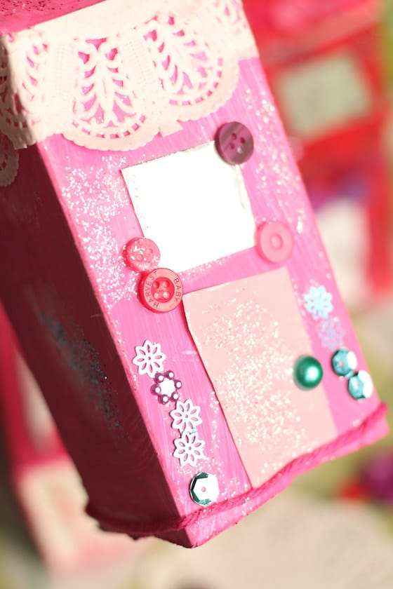 Yarn, buttons and sequins on pink milk carton house