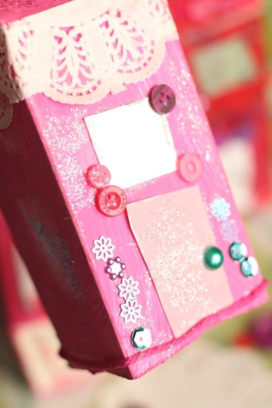 Fils, boutons et paillettes sur maison en carton de lait rose