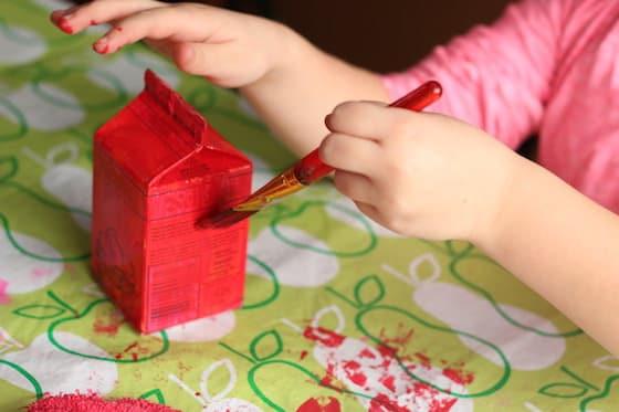 child painting milk carton red