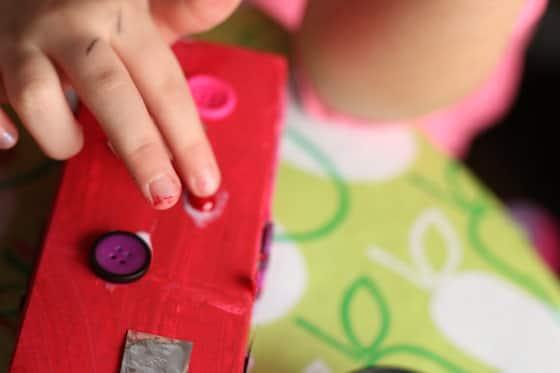 gluing decorative beads on red milk carton