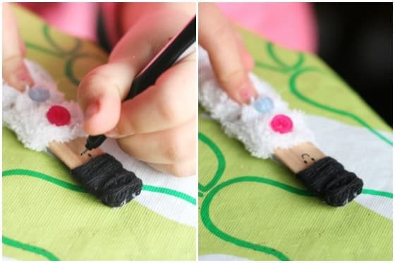 Decorating a craft stick doll with buttons and yarn