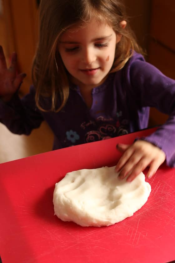 child kneading white clay dough on red cutting mat