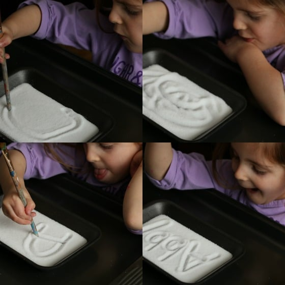 Preschooler drawing shapes and writing her name in a salt tray