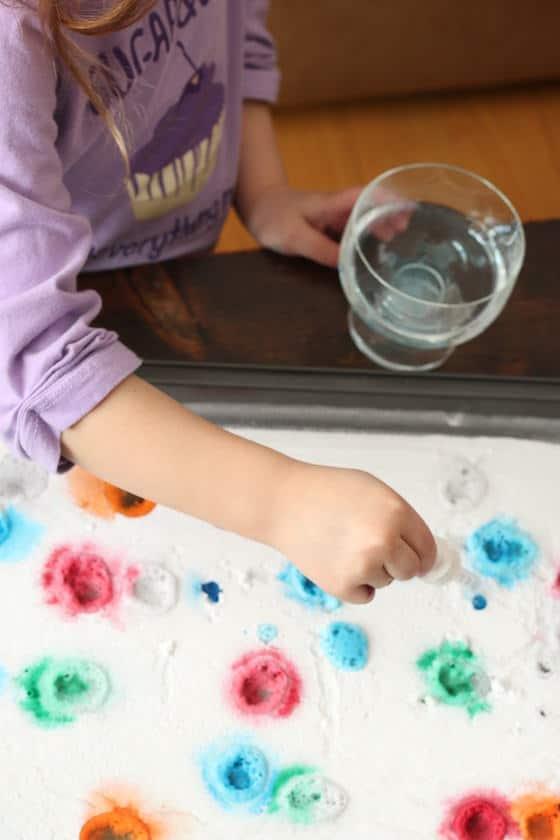 child dripping vinegar on baking soda