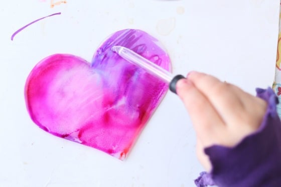child dripping alcohol onto plastic heart coloured with Sharpies