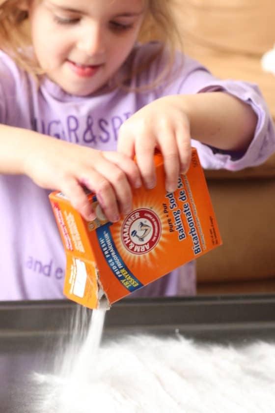 child pouring baking soda on baking sheet