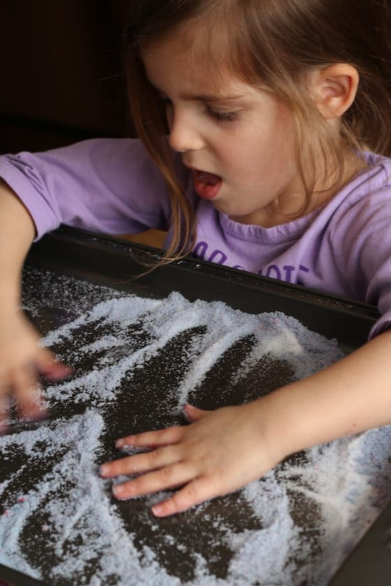 child swishing hands in a baking sheet filled with salt