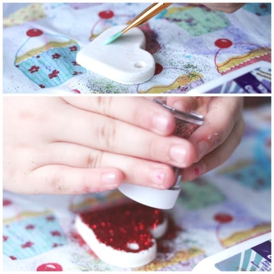 child gluing red glitter on white heart homemade clay ornament