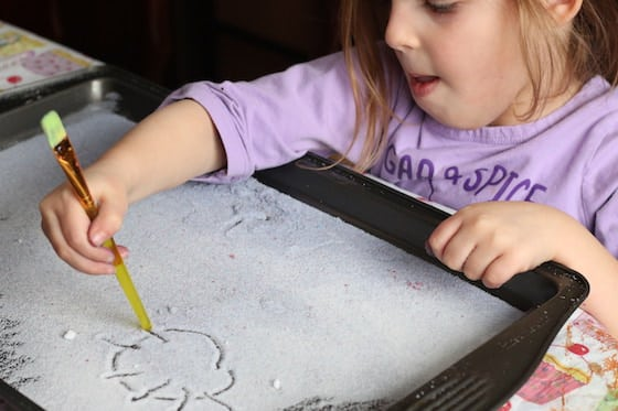 preschooler drawing a sun in a tray of salt