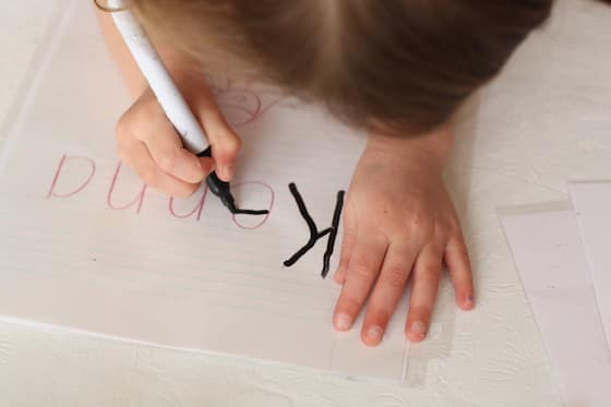 Child practicing writing her name