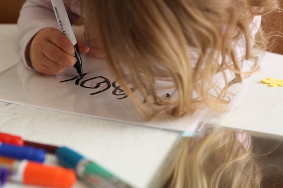 Child tracing the letters of her name