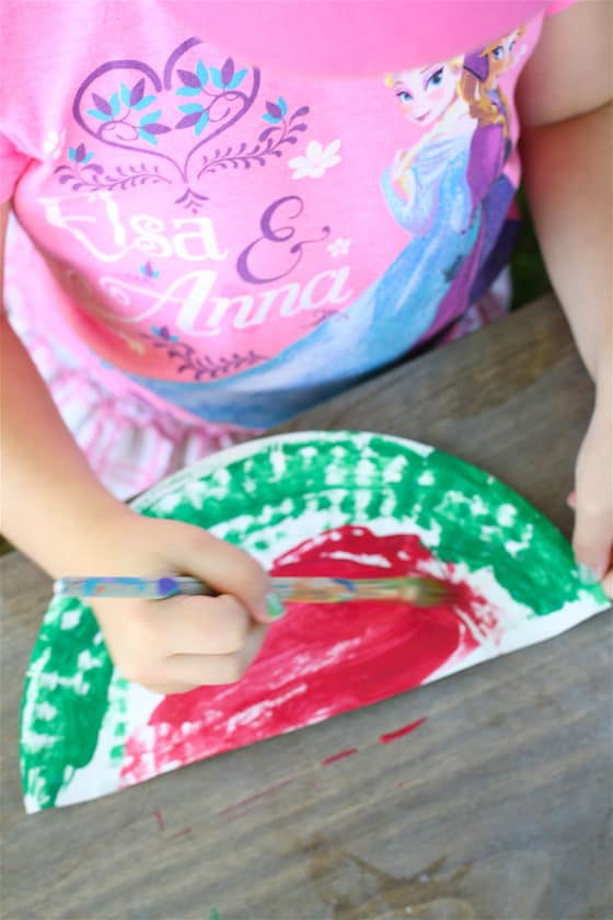 child making a watermelon out of a paper plate