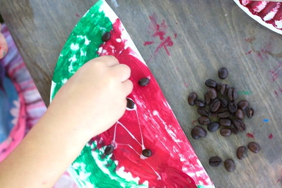 Preschooler gluing coffee beans on a paper plate watermelon