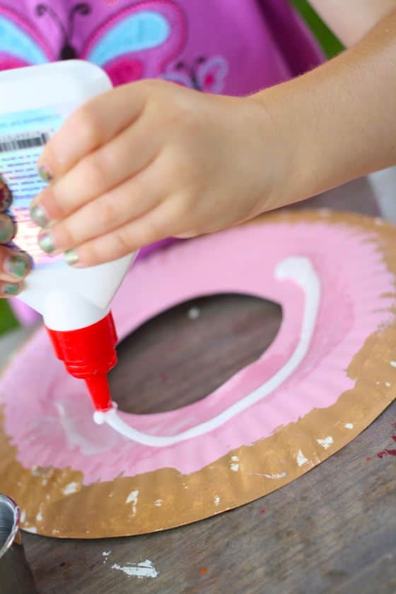 child squeezing glue onto paper plate