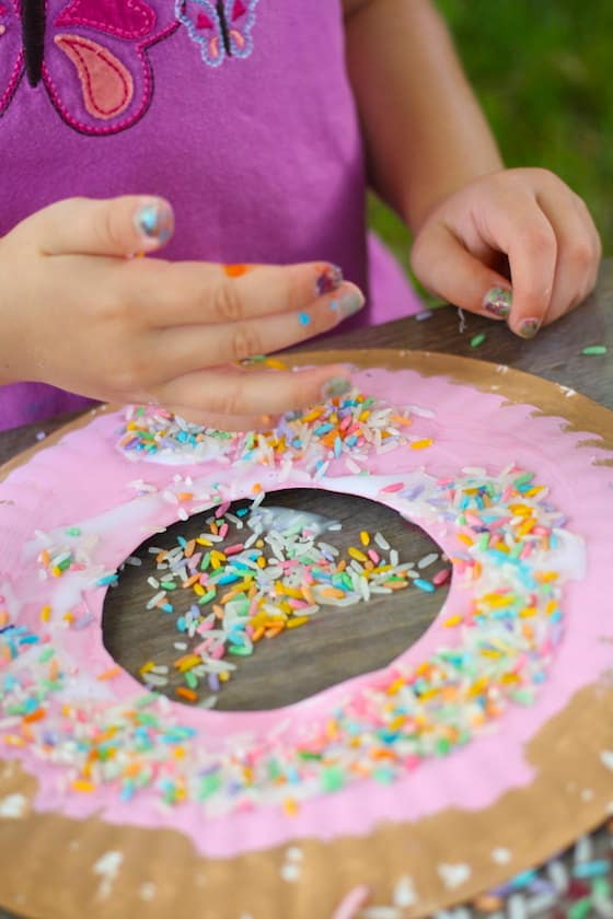 child sprinkling coloured rice onto a paper plate donut craft & Paper Plate Donut Craft for Kids - Happy Hooligans