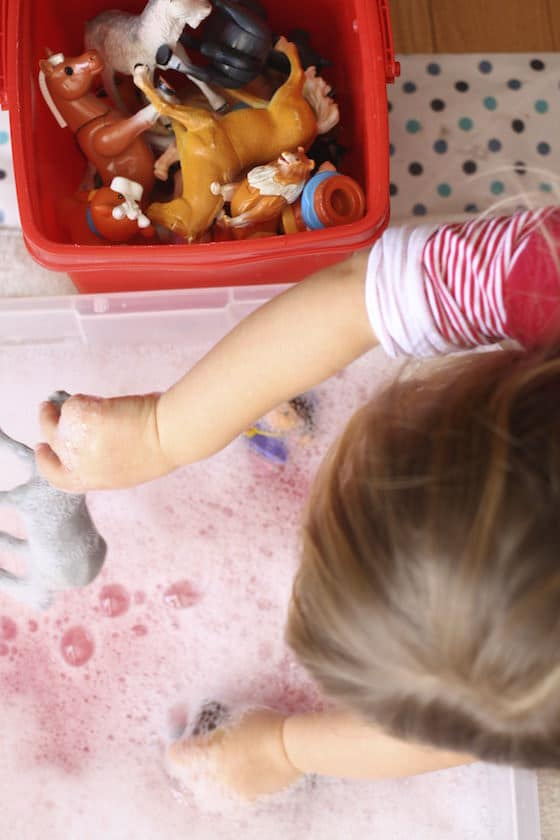 Kids washing toys in basin of soapy water