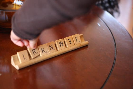 child placing scrabble tiles on wooden scrabble tray