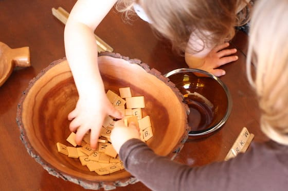 kids digging into bowl filled with scrabble tiles
