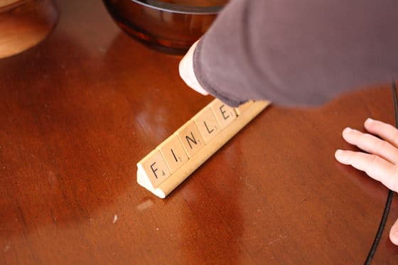 3 year old spelling her name with scrabble tiles