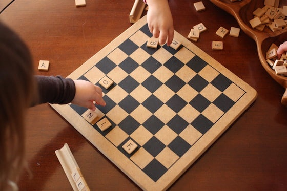 children placing scrabble letters on a checkerboard