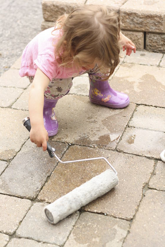 child playing with paint roller and water