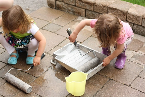 kids rolling paint rollers in water