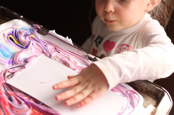 Child pressing paper into shaving cream and food colouring