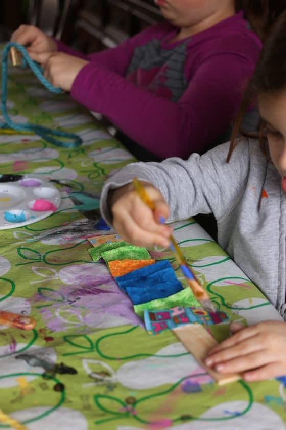 preschooler gluing fabric scraps to a paint stick