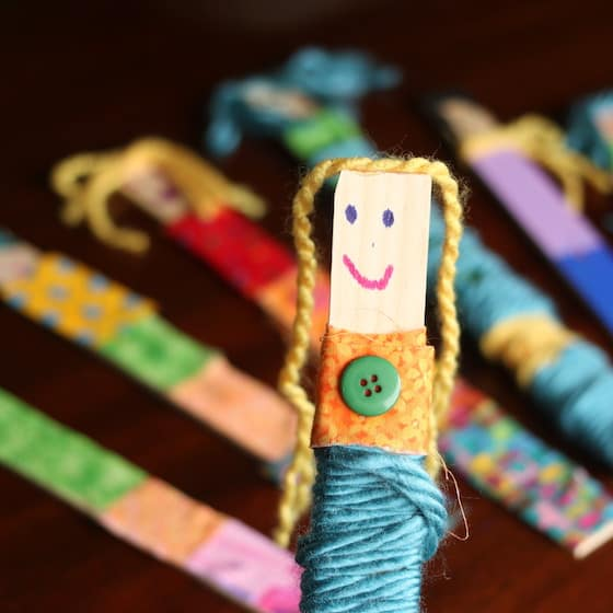 craft stick doll wrapped in fabric and yarn with button glued on