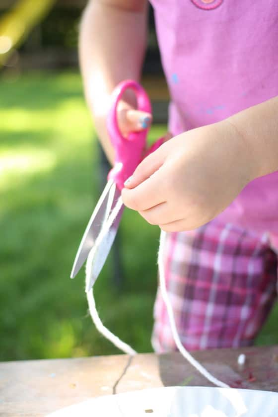 child cutting yarn with scissors for paper plate kite