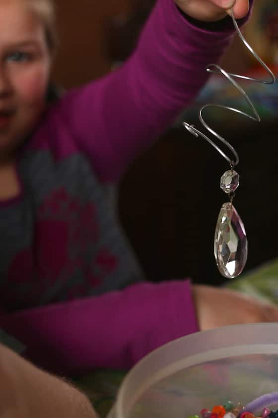 child holding chandelier bauble threaded onto wire