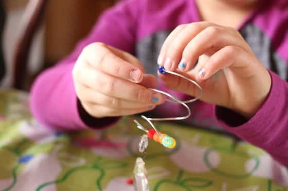 child threading beads onto florist wire spiral