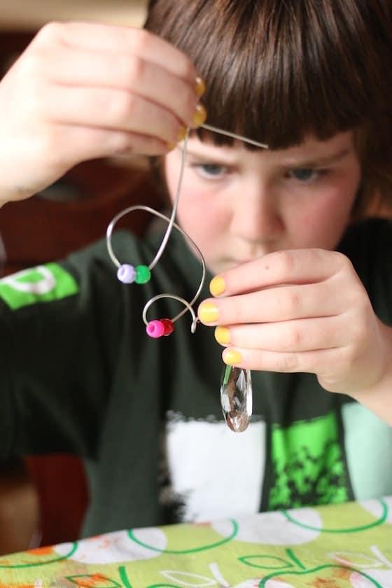 child threading pony beads onto thin guaged wire