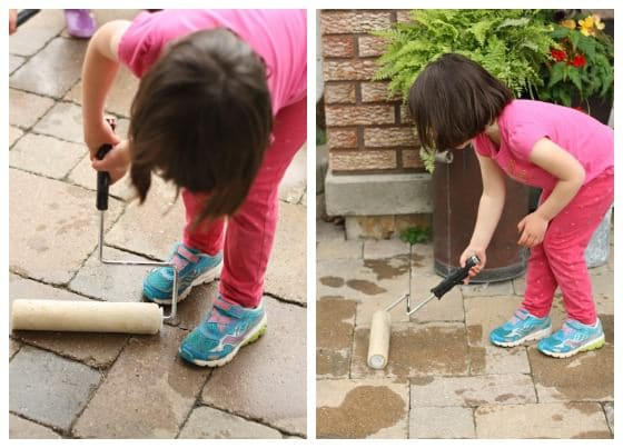 painting the sidewalk with paint rollers and water