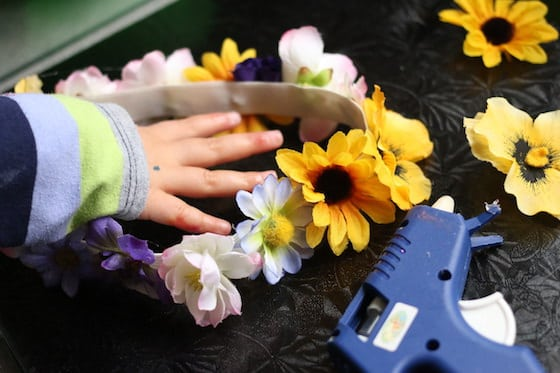 child gluing flowers to waistband elastic to make a flowered tiara for dress up play