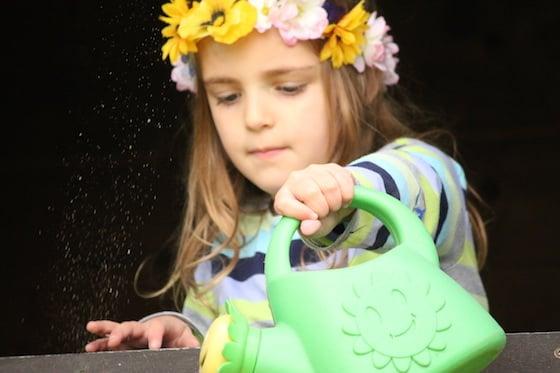 child watering flowers wearing hand made flowered tiara