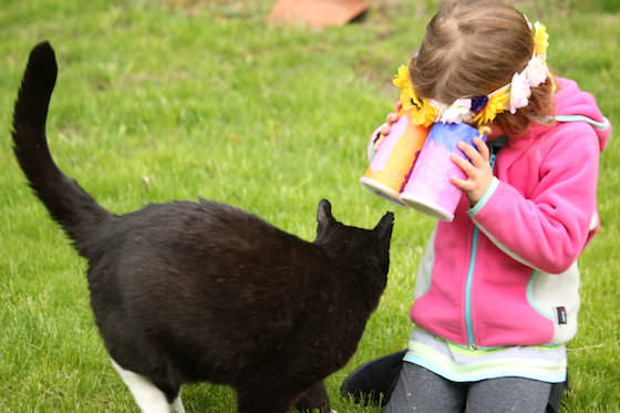 kid looking at cat through toy binoculars