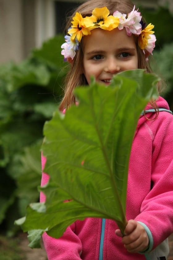 child wearing homemade tiara and holding huge rhubarb leaf