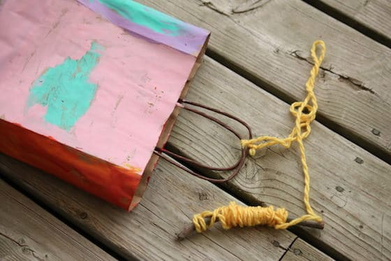 Stick, yarn and painted paper gift bag