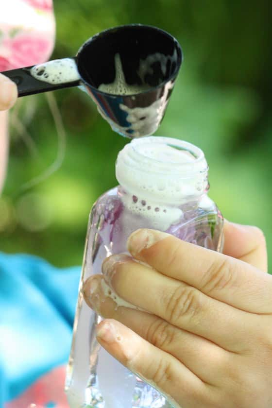 child stirring soapy water in glass bottle