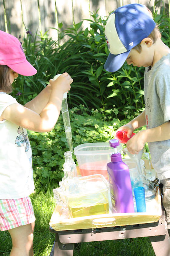 kids using basters to transfer coloured water into glass jars