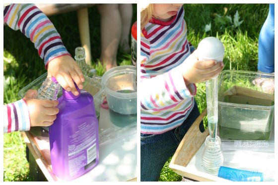 toddler adding soap and coloured water to glass bottles