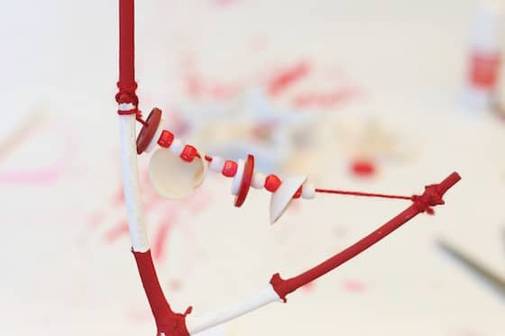 Y-shaped stick painted red and white, and strung with red and white beads, buttons and shells