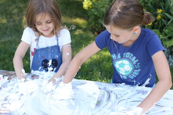 kids cleaning art table with shaving cream