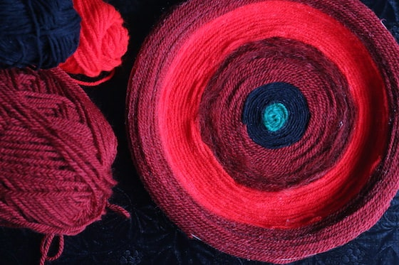 finished yarn poppy beside red and black balls of yarn