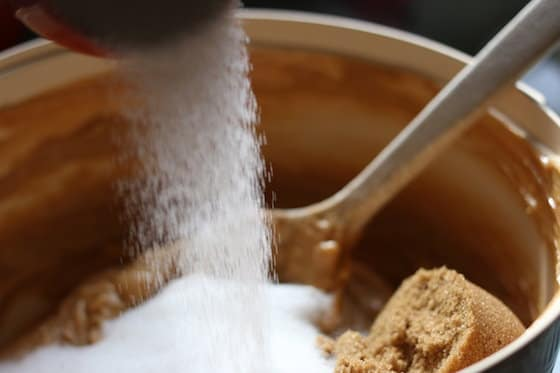 pouring white sugar into peanut butter cookies dough
