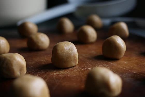 Rolled balls of peanut butter cookie dough on baking stone